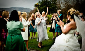 Bride throwing bouquet in wedding photograph